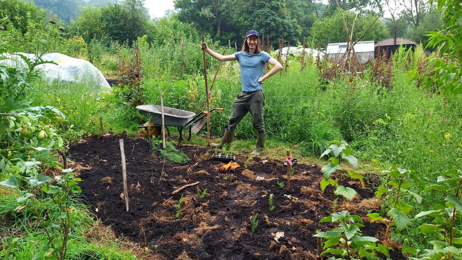 A man poses with a wheelbarrow and hoe in front of a small vegetable patch