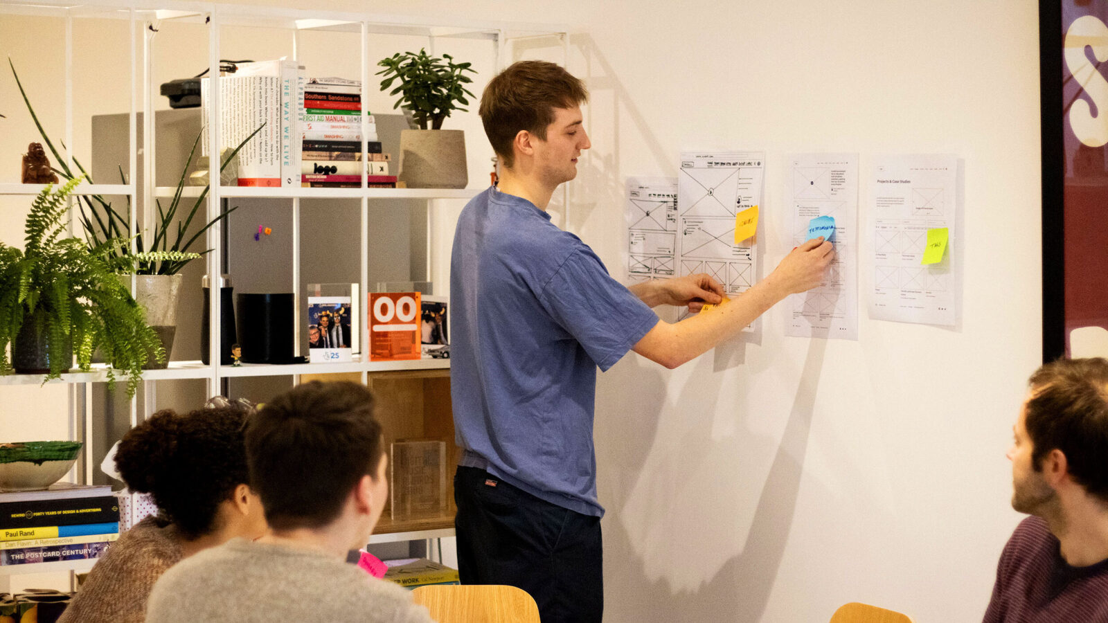 A team of web designers discuss wireframe designs by pinning them to the wall