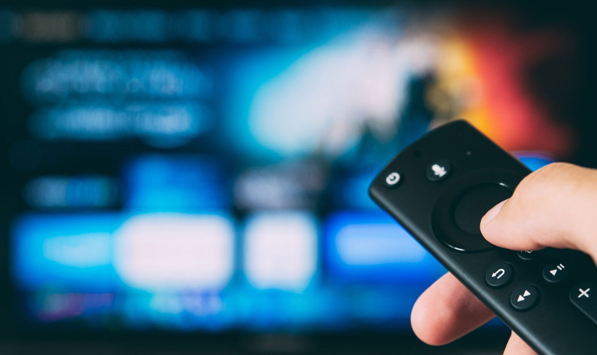 Hand holding a remote control with a blurred video on demand user interface in the background