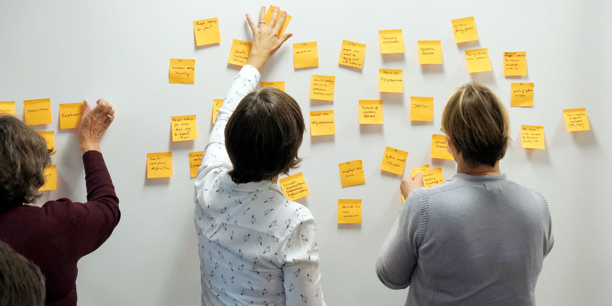 Three women post ideas to the wall on post-it notes