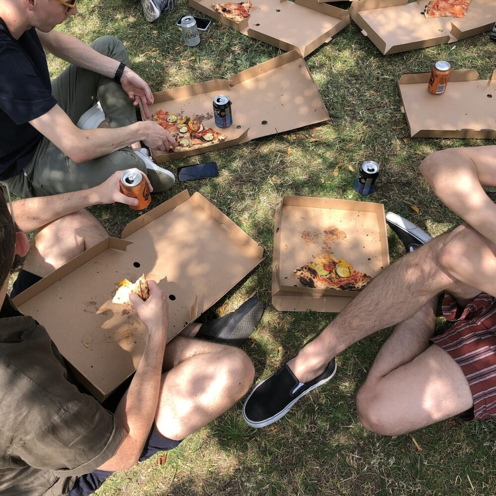 Several people sitting in the shade of a tree eating pizza from cardboard boxes