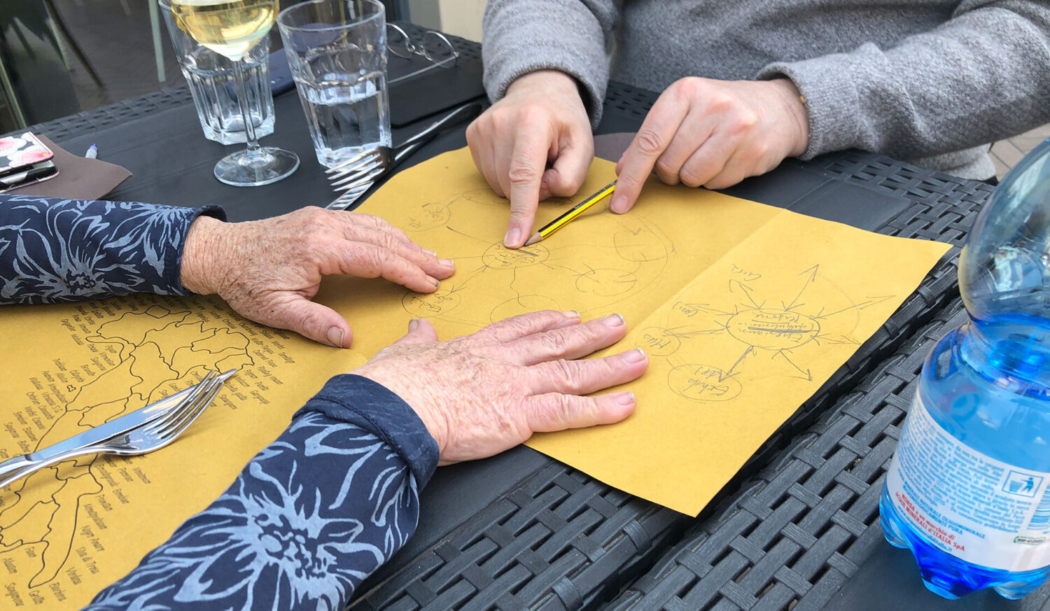 Two people plan a digital strategy on the back of a paper placemat on paper over lunch