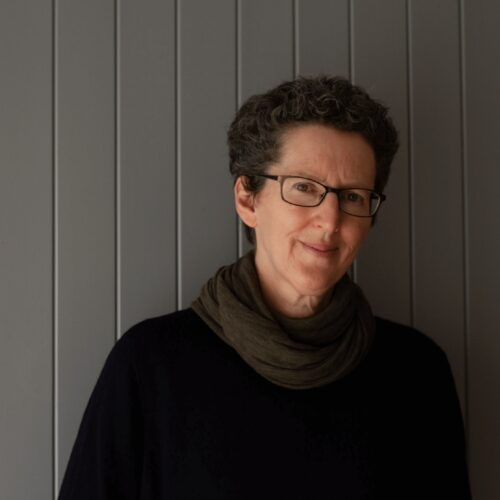 Colour portrait of Juliette Mitchell in a black top and brown scarf against a grey background