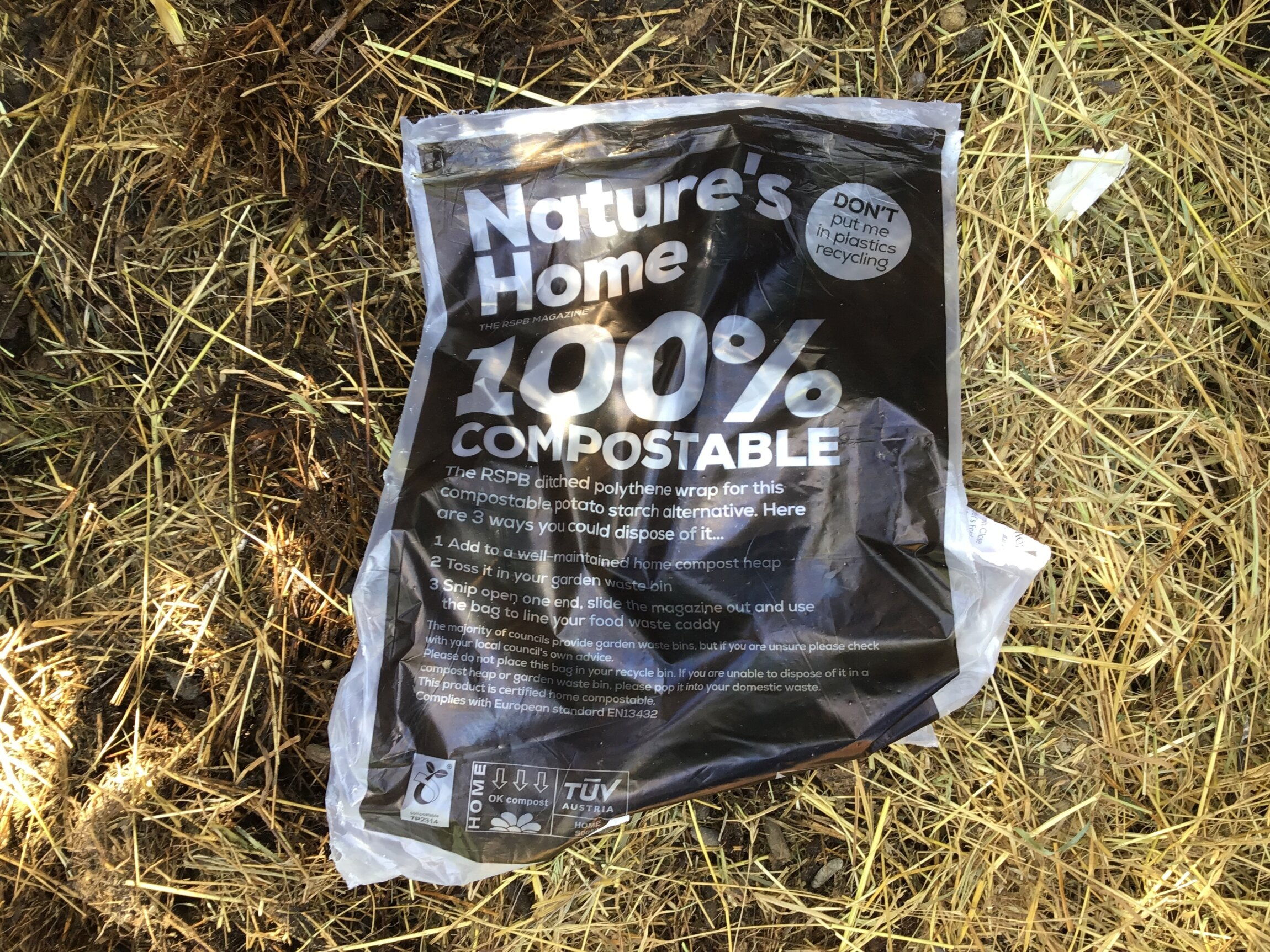 A compostable potato starch bag on a background of straw