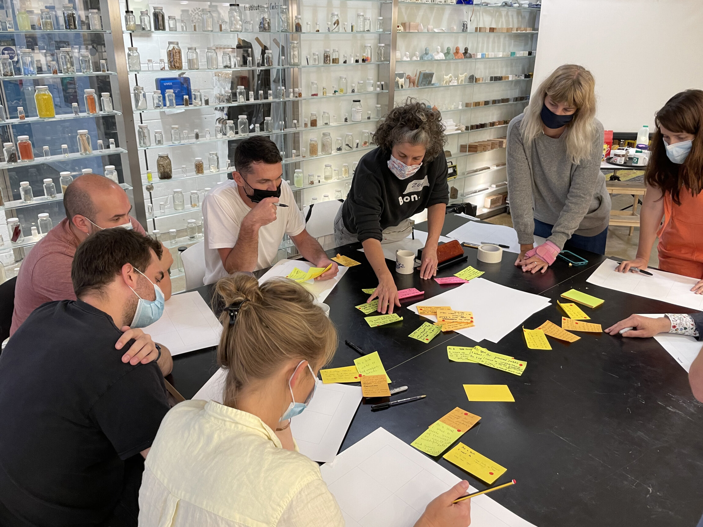 Women and men collaborate on a user experience workshop, post its and notebooks are strewn over a table